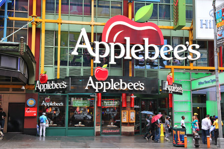 A street view picture of the Applebee's restaurant in Times Square, New York. It is one of a kind and extra colorful. A huge Applebee's logo overhangs the sidewalk with three smaller ones on a marquee just below. It is raining, the sidewalk is slick and passersby are carrying umbrellas.