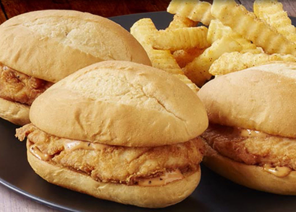 Picture of a Zaxbys Nibbler Sandwich. It is a chicken finger tucked in a toasted bun and topped with Zax Sauce.