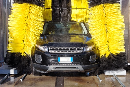 Black vehicle emerging from a car wash with bright yellow brushes spinning against top and side of car.