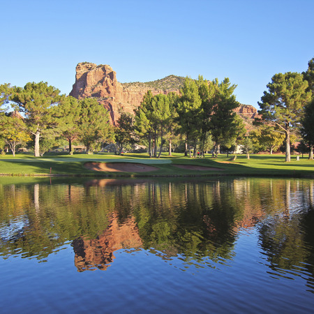 Oakcreek Country Club Sedona. Red rocks on golf course reflect on large pond in foreground