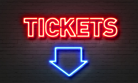 Red neon lettered TICKETS sign mounted on brick wall with blue neon arrow pointed down at picture caption.