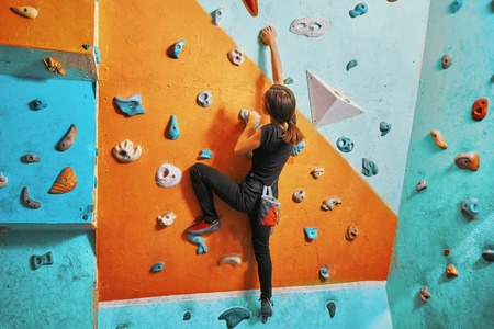 Young woman climbing a colorful indoor rock wall at AZ on the Rocks.