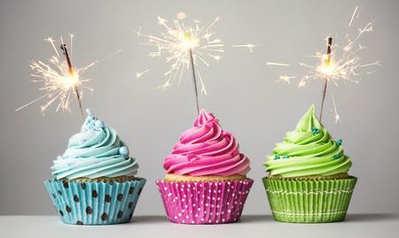 Three birthday cupcakes, each with a different color frosting: blue, pink and green. Instead of candles each has a burning sparkler placed at an angle on top.