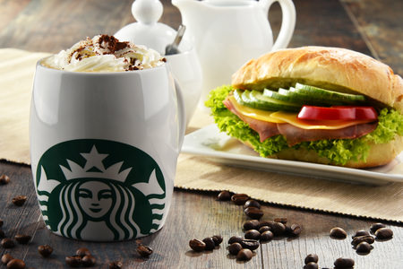 A ham, American cheese and vegetable sandwich on a plate beside a whipped cream and chocolate topped hot Starbucks beverage.